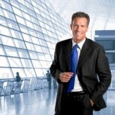 8235328-mature-successful-businessman-smiling-and-looking-at-camera-in-a-modern-office-building